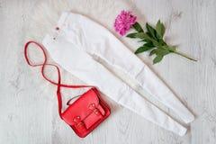 Jeans blancs, sac à main rouge et pivoine sur un fond clair, concept à la mode Images libres de droits