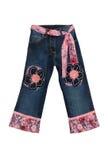 Jeans bleus de fille d'enfants avec la configuration de fleurs rose d'isolement sur W Photos libres de droits
