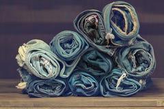 Jeans blu del denim del rotolo sistemati in pila Sul fondo di struttura di legno di quercia, Jeans strappati di uno spazio della  Fotografia Stock