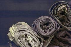 Jeans blu del denim del rotolo sistemati in pila Sul fondo di struttura di legno di quercia, Jeans strappati di uno spazio della  Immagini Stock