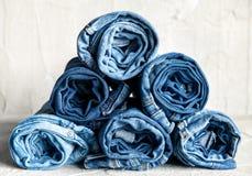 Jeans blu del denim del rotolo su fondo grigio Fotografia Stock