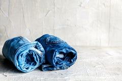 Jeans blu del denim del rotolo su fondo grigio Immagine Stock