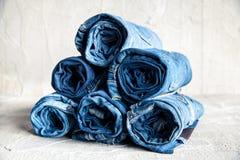 Jeans blu del denim del rotolo su fondo grigio Fotografie Stock Libere da Diritti
