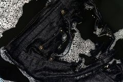 Jeans blue dark soak in sponge washing and wet in sponge water dirty black, Colored jeans clothes royalty free stock image