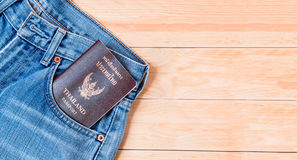 Jeans. Blue jeans with Thailand passport on wooden table Stock Photo