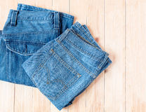 Jeans. Blue jeans on wooden background Royalty Free Stock Photography
