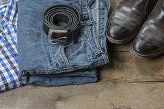 Jeans and Boots. Jeans, leather Boots and Belt on wooden background royalty free stock photography