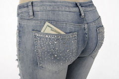 Jeans with money in the pocket. Closeup of woman's jeans with money in the pocketrn royalty free stock images