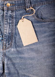 Jeans with Cardboard Labels. Cardboard label attached to old jeans pocket around Stock Images