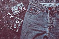 Jeans, cassette sonore, disposition d'écouteurs sur un béton noir image stock