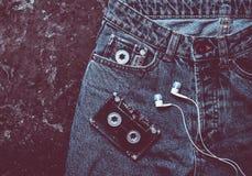 Jeans, cassette sonore, disposition d'écouteurs sur un béton noir photo stock
