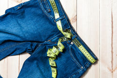 Jeans and centimeter on a wooden background Royalty Free Stock Photo
