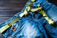 Jeans and centimeter on a wooden background. Royalty Free Stock Photography
