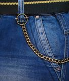 Jeans and chain. Jeans pocket, belt, and a decorative brass keychain Stock Photo