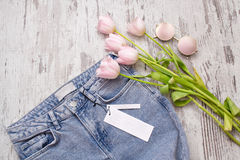 Jeans with a clean tag, pink glasses and tulips on a wooden background. Fashionable concept, top view Royalty Free Stock Image