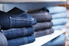 Jeans clothes on shelf in shop. Shoping sale background theme. clothes on hanger in shop Stock Images