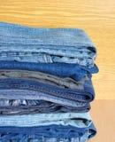 Jeans colorés sur l'étagère de placard, plan rapproché de vue de face Photographie stock libre de droits