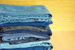 Jeans colorés sur l'étagère de placard, plan rapproché de vue de face Photographie stock