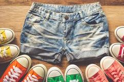 Jeans courts pour des adolescentes et des espadrilles sur les planchers en bois Photo stock