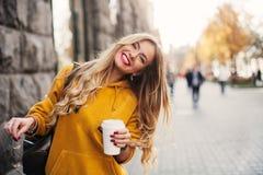 Jeans d'uso del boyfrend della giovane donna felice alla moda, sweetshot giallo luminoso delle scarpe da tennis bianche Tiene il  Fotografia Stock Libera da Diritti