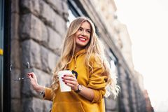 Jeans d'uso del boyfrend della giovane donna felice alla moda, sweetshot giallo luminoso delle scarpe da tennis bianche Tiene il  Fotografia Stock