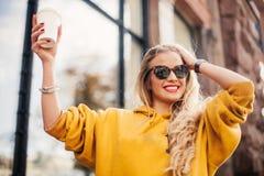 Jeans d'uso del boyfrend della giovane donna felice alla moda, sweetshot giallo luminoso delle scarpe da tennis bianche Tiene il  Fotografie Stock Libere da Diritti