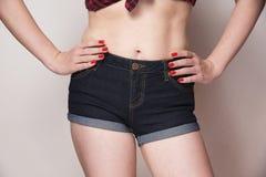 Jeans d'uso della donna con le sue mani sulle anche fotografie stock
