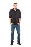 Jeans de jeune homme occasionnel et chemise de plaid de port souriants d'un air affecté avec des mains dans des poches Image stock