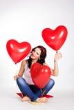 Jeans de port de belle jeune femme de Saint-Valentin et tenir les ballons rouges image stock