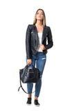 Jeans de port de femme occasionnelle élégante magnifique et veste en cuir tenant le sac à main noir Photographie stock libre de droits