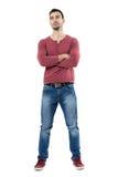 Jeans de port de sourire d'homme occasionnel de jeunes heureux avec les bras croisés recherchant Photo libre de droits