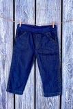 Jeans del neonato che appendono sulla corda Immagini Stock