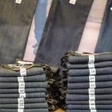 Jeans della raccolta del denim delle blue jeans impilati con la dimensione dell'etichetta Fotografia Stock