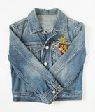 Jeans denim woman jacket with vintage brooches on white background. Fashion outfit Stock Image