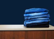 Jeans die op blauwe achtergrond wordt ge?soleerd Jeans die op een lichte achtergrond worden gestapeld De achtergrond van jeans St stock afbeeldingen