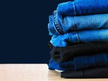 Jeans die op blauwe achtergrond wordt ge?soleerd Jeans die op een lichte achtergrond worden gestapeld De achtergrond van jeans St stock foto's