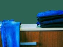 Jeans die op groene achtergrond wordt ge?soleerd Jeans die op een lichte achtergrond worden gestapeld De achtergrond van jeans St stock fotografie