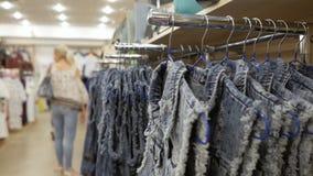 Jeans die op hangers op het rek in de kledingsopslag hangen stock video