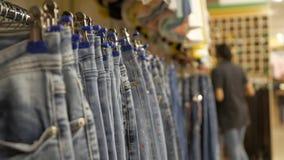 Jeans die op hangers op het rek in de kledingsopslag hangen stock footage