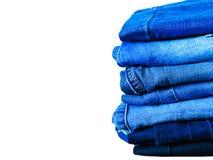 Jeans die op witte achtergrond wordt ge?soleerdt Jeans die op een lichte achtergrond worden gestapeld De achtergrond van jeans St stock fotografie