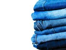 Jeans die op witte achtergrond wordt ge?soleerdt Jeans die op een lichte achtergrond worden gestapeld De achtergrond van jeans St royalty-vrije stock afbeeldingen