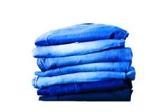 Jeans die op witte achtergrond wordt ge?soleerdt Jeans die op een lichte achtergrond worden gestapeld De achtergrond van jeans St royalty-vrije stock foto's