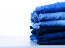 Jeans die op witte achtergrond wordt ge?soleerdt Jeans die op een lichte achtergrond worden gestapeld De achtergrond van jeans St stock afbeelding