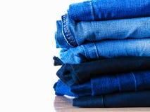 Jeans die op witte achtergrond wordt ge?soleerdt Jeans die op een lichte achtergrond worden gestapeld De achtergrond van jeans St royalty-vrije stock afbeelding