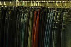 Jeans of different colors on hangers in a clothing store. Tinted in a yellow dark key. Background for design on the theme of fashi. Jeans of different colors on stock photos