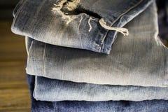 Jeans differenti piegati su un fondo di legno Immagine Stock