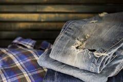 Jeans differenti piegati su un fondo di legno Fotografia Stock Libera da Diritti