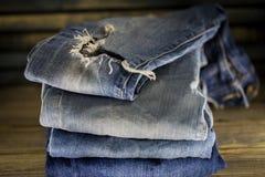 Jeans differenti piegati su un fondo di legno Immagini Stock Libere da Diritti