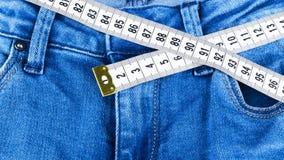 Jeans e righello di una donna del blu, concetto della dieta e perdita di peso Jeans con nastro adesivo di misurazione Stile di vi fotografia stock