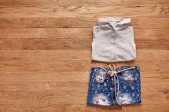 Jeans e rivestimento del ` s dei bambini su fondo di legno Fotografia Stock Libera da Diritti